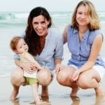 women on the beach with baby